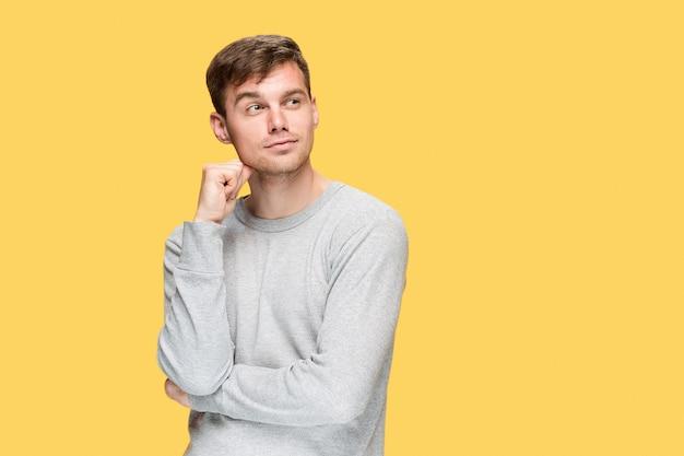 Молодой человек улыбается и смотрит в желтую студию