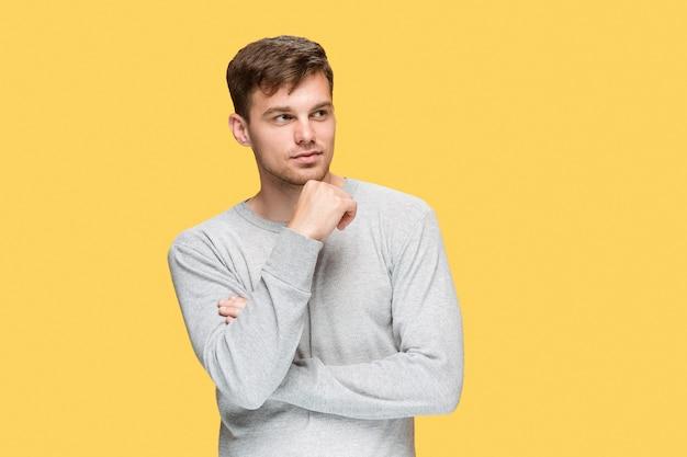 Молодой человек улыбается и смотрит в сторону