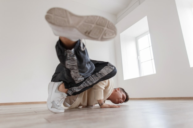 Молодой человек стоит на одной руке и поднимает обе ноги в белом пуловере и стильных кроссовках.