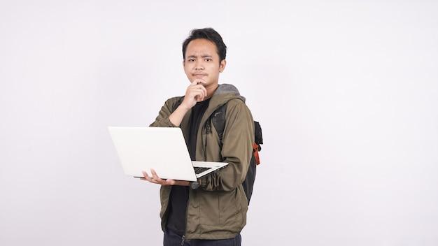 젊은 남자는 노트북으로 공백을 생각하면서 가방을 입고 있었다