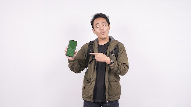 白いスペースに隔離されたバッグを身に着けている若い男は、グリーンスクリーンの電話を指摘しました