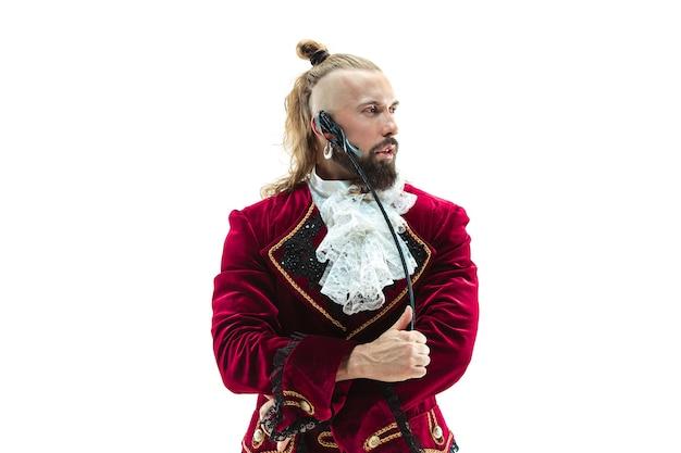 鞭でスタジオでポーズをとる侯爵の伝統的な中世の衣装を着た若い男。ファンタジー、アンティーク、ルネッサンスのコンセプト 無料写真