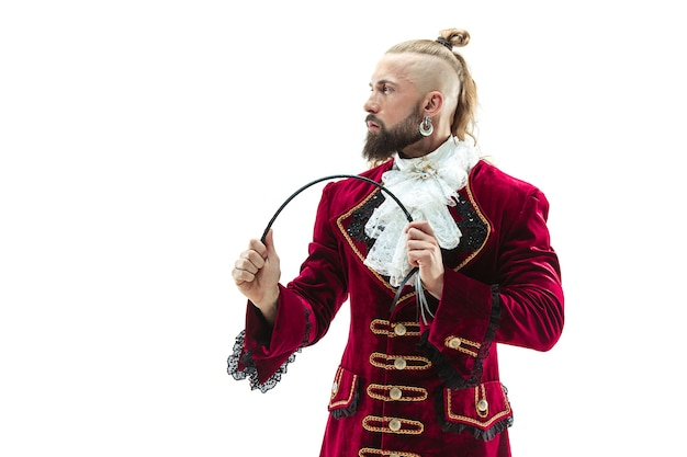 Молодой человек в традиционном средневековом костюме маркиза позирует в студии с кнутом.