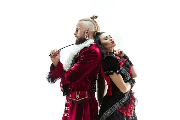 侯爵として女性と一緒にスタジオでポーズをとる侯爵の伝統的な中世の衣装を着た若い男。ファンタジー、アンティーク、ルネッサンスのコンセプト
