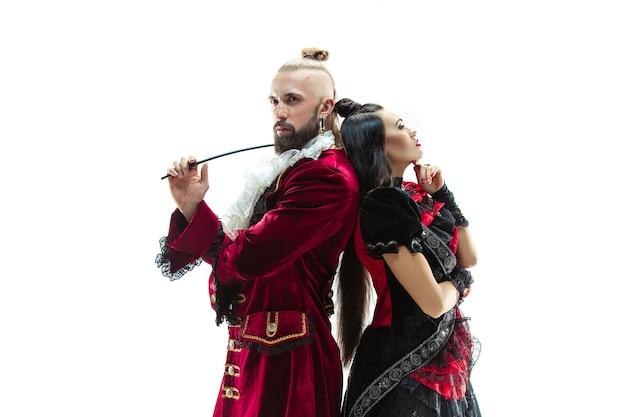 侯爵として女性と一緒にスタジオでポーズをとる侯爵の伝統的な中世の衣装を着た若い男