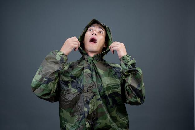청년은 위장 비옷을 입고 다른 제스처를 보여줍니다.