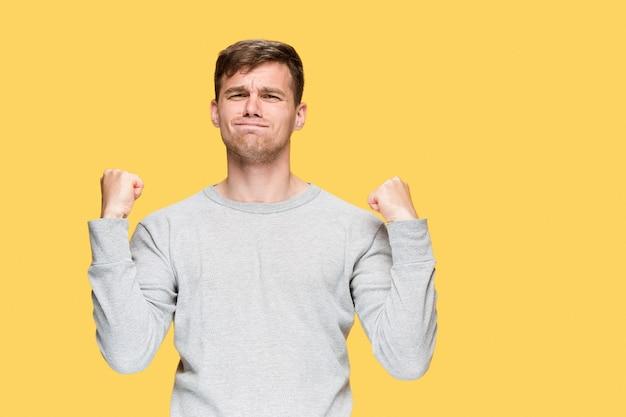 黄色のスタジオの背景に上げられた握りこぶしを持つ若い男