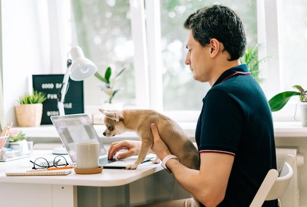 Молодой человек с собакой c печатает на ноутбуке