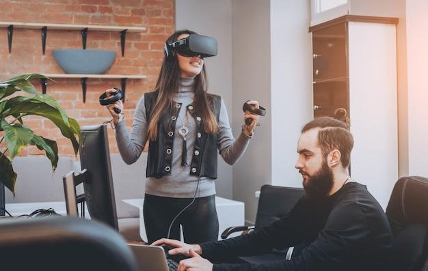 Молодой человек с подругой играет в игру в офисе.