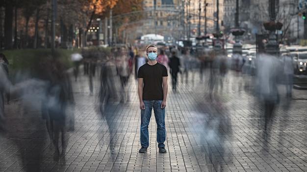 의료용 안면 마스크를 쓴 청년이 붐비는 거리에 서 있다