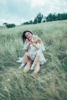 緑の芝生の上の若い母と娘