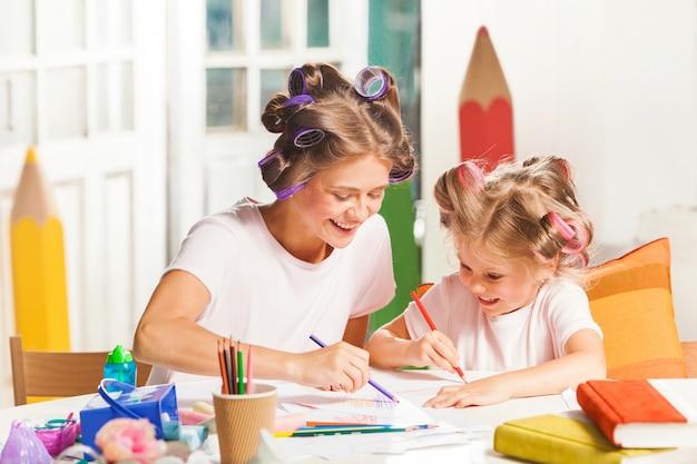 Молодая мама и ее маленькая дочь рисуют карандашами дома
