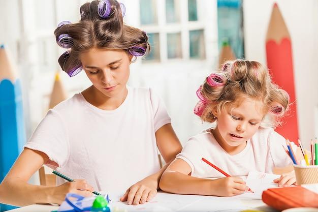 若い母親と自宅で鉛筆で描く彼女の小さな娘