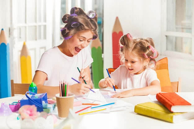 Молодая мать и ее маленькая дочь рисуют карандашами дома