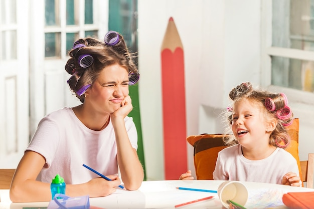 집에서 연필로 그리는 젊은 어머니와 그녀의 작은 딸