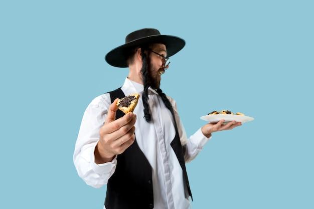 푸림의 유대인 축제를 위해 hamantaschen 쿠키와 검은 모자를 쓴 젊은 정통 유대인 남자