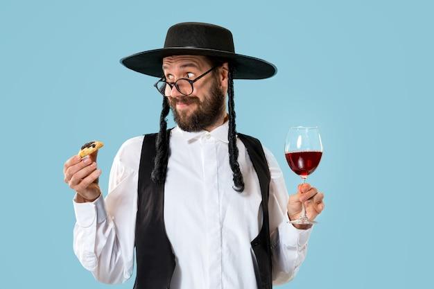 プリムのユダヤ人の祭りのためのハマンタッシェンクッキーと黒い帽子を持つ若い正統派ユダヤ人の男