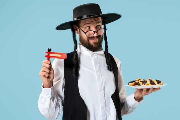 祭りプリムのためのハマンタッシェンクッキーを持つ若い正統派ユダヤ人