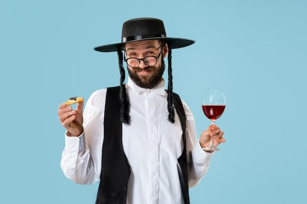 祭りプリムのためのハマンタッシェンクッキーを持つ若い正統派ユダヤ人。