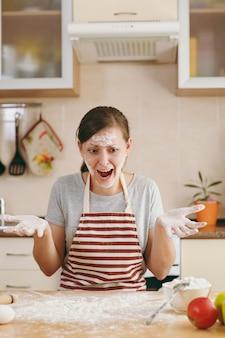 Молодая растерянная и растерянная женщина сидит за столом с мукой и собирается готовить на кухне лепешки. готовим дома. готовить пищу.