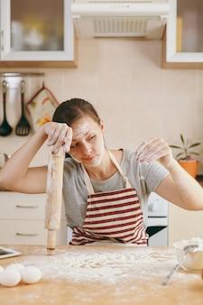 Молодая растерянная и растерянная женщина сидит за столом со скалкой и мукой и собирается готовить на кухне лепешки. готовим дома. готовить пищу.