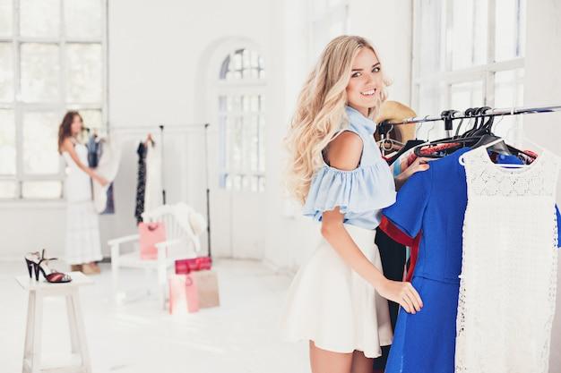 若いきれいな女の子を選択してショップでドレスを試着