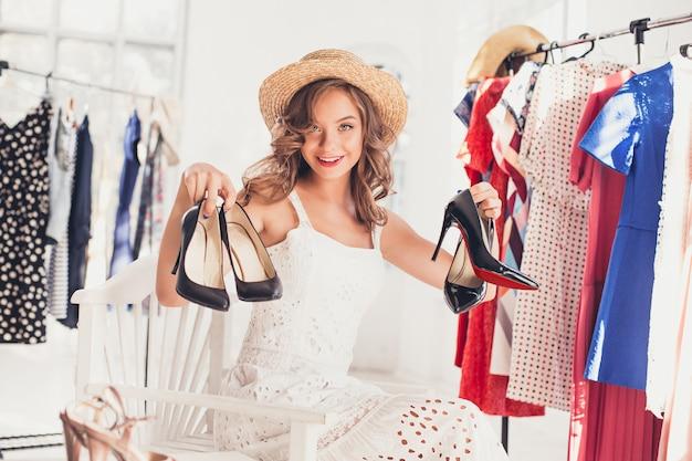 Молодая милая девушка выбирая и примеряя модельные ботинки на магазине