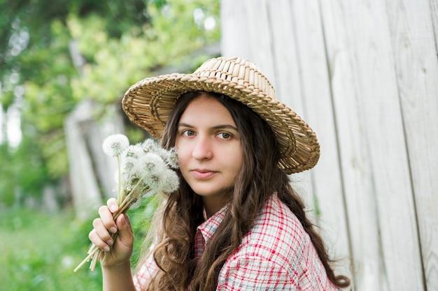 タンポポを持つ若いかわいい女の子。村の夏時間。