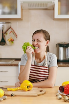 台所で彼女の口にレタスの葉を持つエプロンの若いきれいな女性。ダイエットの概念。健康的な生活様式。家で料理。食べ物を用意します。