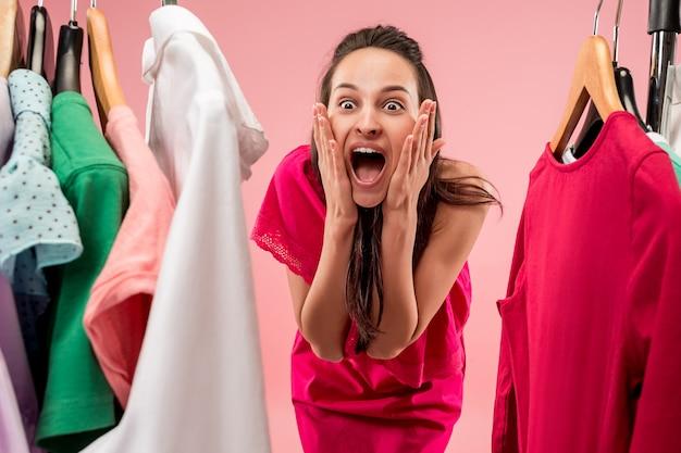若いきれいな女性のドレスを見て、店で選びながら試してみる