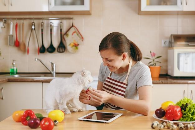 Молодая красивая женщина с белым персидским котом на кухне с таблеткой на столе. овощной салат. концепция диеты. здоровый образ жизни. готовим дома. готовить пищу.