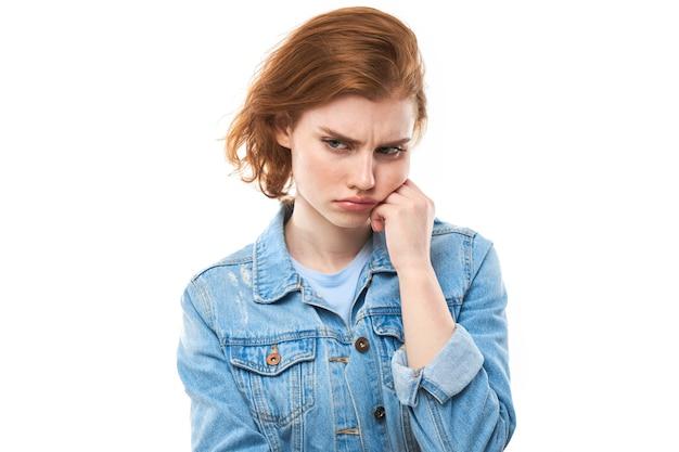 Молодая рыжеволосая женщина задумалась. обида и разочарование. девушка-модель в синей джинсовой куртке на белом фоне. у меня болит зуб