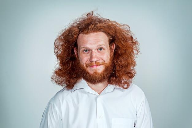 Молодой улыбающийся человек с длинными рыжими волосами, смотрящий в камеру