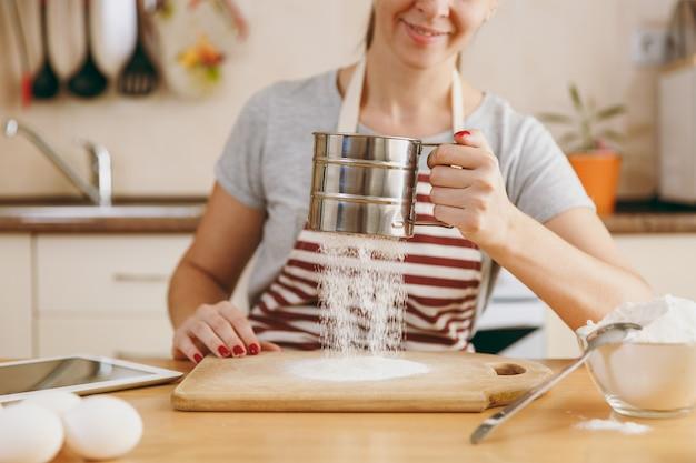 Молодая улыбающаяся женщина просеивает муку железным ситом с таблеткой на столе на кухне. готовим дома. готовить пищу.