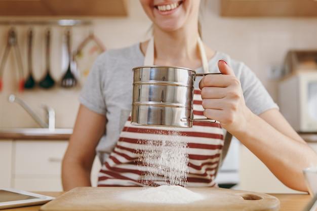 웃고 있는 젊은 여성은 부엌에 있는 탁자 위에 태블릿을 놓고 철체로 밀가루를 체로 친다. 집에서 요리. 음식을 준비하다.