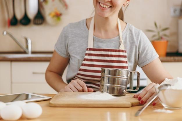 부엌에 있는 탁자에 쇠로 된 체와 밀가루를 들고 웃고 있는 젊은 여성. 집에서 요리. 음식을 준비하다.