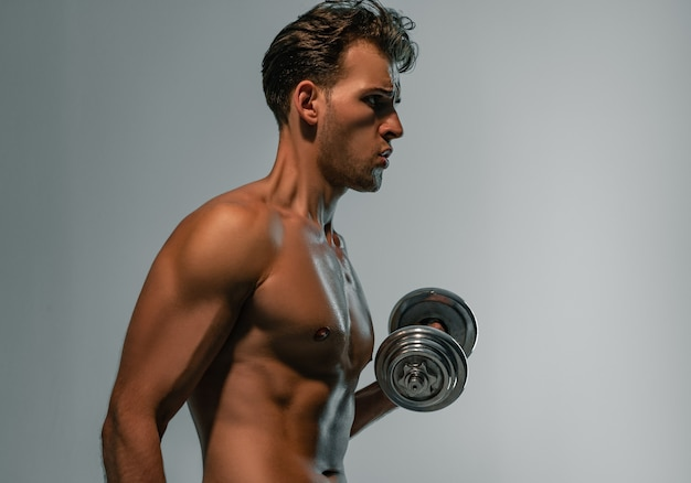 若いスポーツマンはダンベルで訓練します