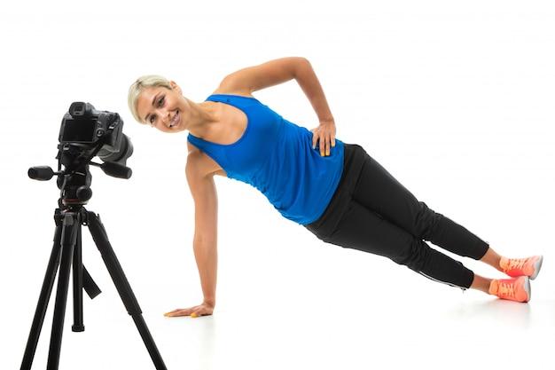 Молодая спортивная девушка со светлыми волосами в черной спортивной теме, черных леггинсах и ярких кроссовках выполняет зарядку перед камерой.