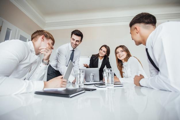 Молодая успешная бизнес-команда на встрече улыбается и обсуждает бизнес