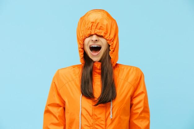 블루에 고립 된가 재킷에 스튜디오에서 젊은 놀된 커플. 인간의 행복 긍정적 인 감정. 추운 날씨의 개념. 여성 및 남성 패션 개념