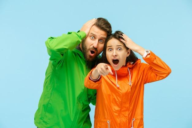 カメラを指して、青で隔離の秋のジャケットを着てスタジオでポーズをとって驚いた若いカップル。
