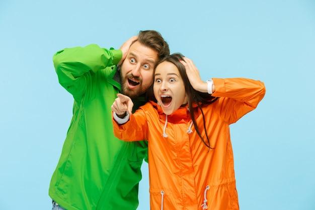 左を指して、青で隔離された秋のジャケットを着てスタジオでポーズをとっている若い驚きのカップル。人間の否定的な感情。寒さの概念。女性と男性のファッションの概念