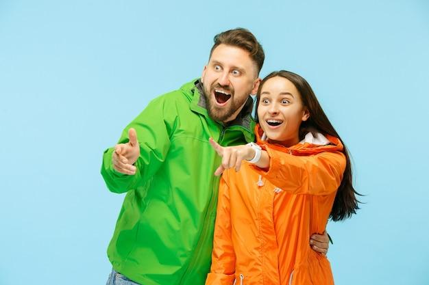 左を指して、青で隔離された秋のジャケットを着てスタジオでポーズをとっている若い驚きのカップル。