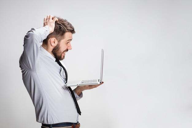 灰色の背景に彼のラップトップコンピューターを持つ若い驚いた男