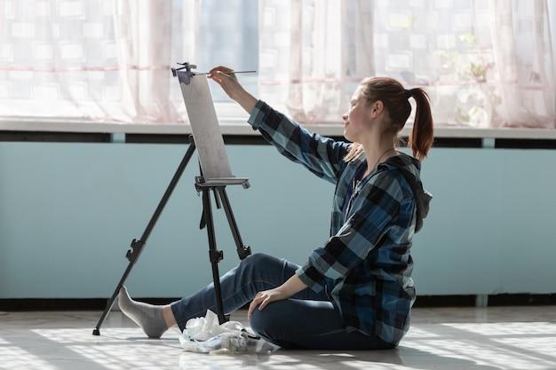 젊은 십 대 여자 예술가 대리석 타일의 바닥에 앉아있다. 오일 페인트로 페인팅하는 과정에서 여자.