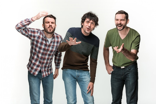 Молодые трое мужчин улыбаются, стоя на белом с разными эмоциями
