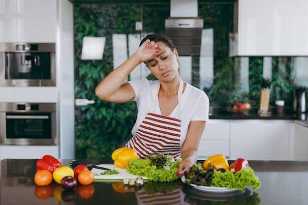 台所のエプロンで疲れた若い女性