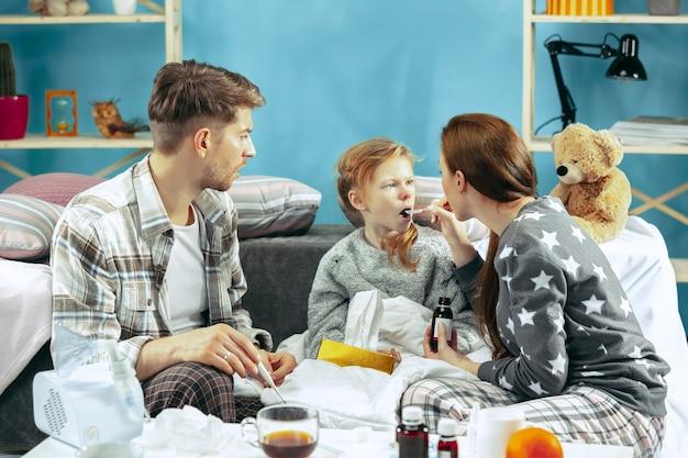 Молодая женщина и мужчина с больной дочерью дома. домашнее лечение. борьба с болезнью. медицинское здравоохранение. семейная болезнь. зима, грипп, здоровье, боль, отцовство, концепция отношений