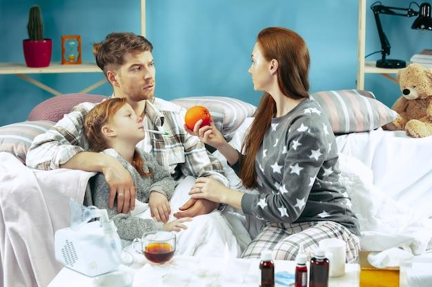 Молодая женщина и мужчина с больной дочерью дома. домашнее лечение. борьба с болезнью. медицинское обслуживание