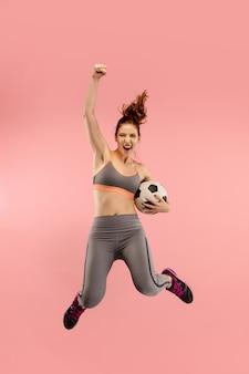 Молодая женщина как футболист футболист прыгает и пинает мяч в студии на красном фоне.